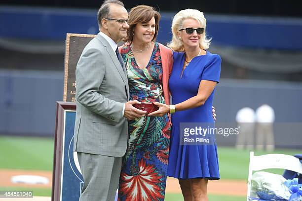 Joe Torre former manager of the New York Yankees is given a gift from Jennifer Steinbrenner Swindal right during Joe Torre Day prior to the game...