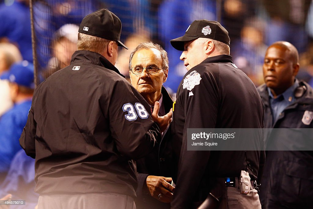 Joe Torre, Major League Baseball's Chief Baseball Officer, meets with umpires in the fourth inning to discuss technical difficulties during Game One of the 2015 World Series between the Kansas City Royals and the New York Mets at Kauffman Stadium on October 27, 2015 in Kansas City, Missouri.