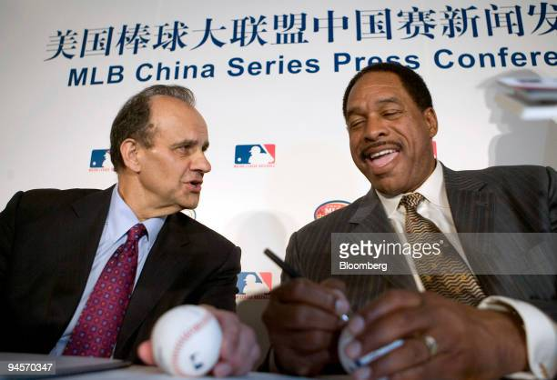 Joe Torre manager of the Los Angeles Dodgers speaks with Dave Winfield vice president of the San Diego Padres and former baseball player as Winfield...