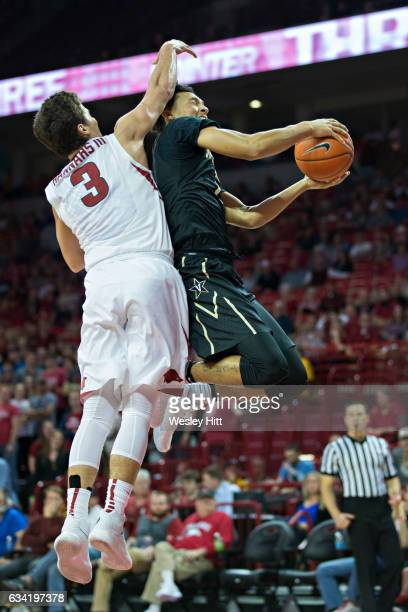 Joe Toye of the Vanderbilt Commodores goes up for a shot and is fouled by Dusty Hannahs of the Arkansas Razorbacks at Bud Walton Arena on February 7...