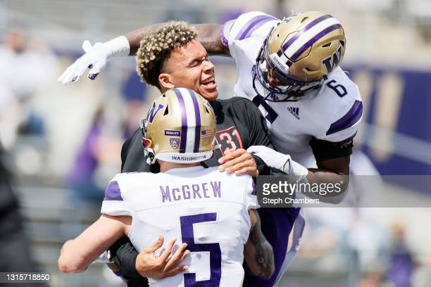 Joe Tryon, former linebacker of the Washington Huskies, is bombarded by running back Sean McGrew and running back Richard Newton after Tryon was...