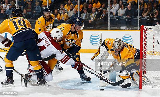 Joe Vitale of the Arizona Coyotes has his shot blocked by goalie Pekka Rinne as Roman Josi of the Nashville Predators defends at Bridgestone Arena on...