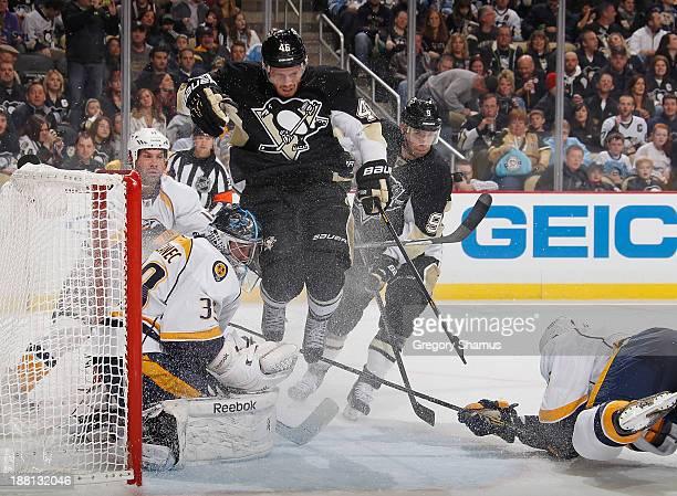 Joe Vitale of the Pittsburgh Penguins jumps to avoid a shot in front of goalie Marek Mazanec of the Nashville Predators on November 15 2013 at Consol...