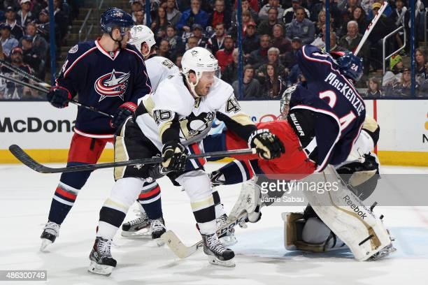 Joe Vitale of the Pittsburgh Penguins knocks Derek MacKenzie of the Columbus Blue Jackets to the ice as goaltender Marc-Andre Fleury of the...