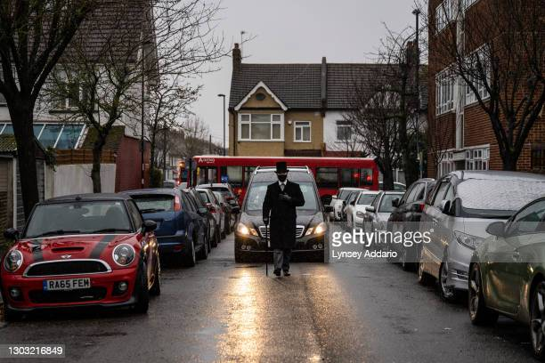 Joe Walkling assistant general manager of Rowland Brothers funeral home, leads a funeral procession past the home of COVID-19 Alan Corbin, who passed...