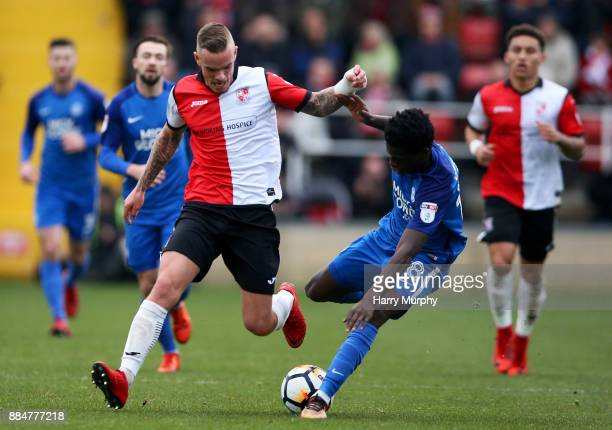 Joe Ward of Woking and Leonardo Da Silva Lopes of Peterborough United vie for the ball during the Emirates FA Cup Second Round match between Woking...