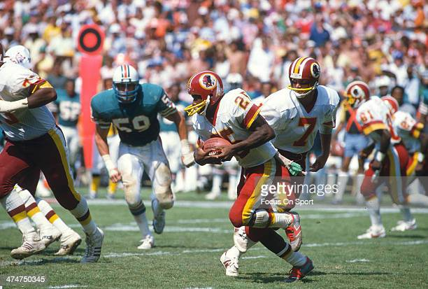 Joe Washington of the Washington Redskins carries the ball against the Miami Dolphins during an NFL football game September 2 1984 at RFK Stadium in...