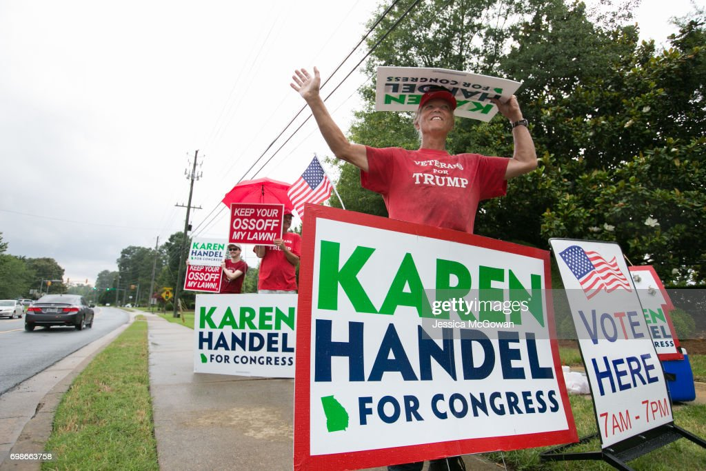 Joe Webb of Marietta, a supporter of Republican candidate Karen Handel waves campaign signs outside of the East Cobb Government Center on June 20, 2017 in Marietta, Georgia. Handel and Ossoff are running against each other in a special election to fill the congressional seat vacated by Secretary of Health and Human Services Tom Price.