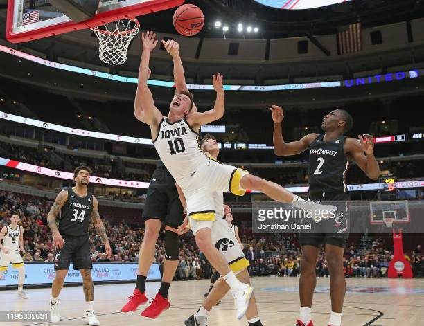 Joe Wieskamp of the Iowa Hawkeyes is fouled while shooting by Chris Vogt of the Cincinnati Bearcats at the United Center on December 21 2019 in...
