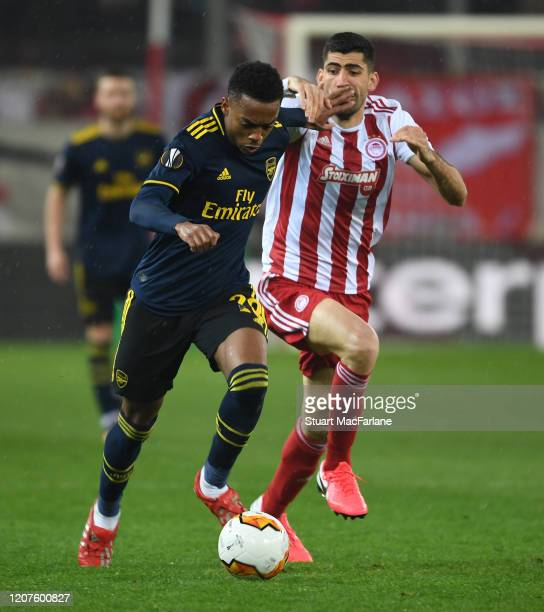 Joe Willock of Arsenal breaks past Andreas Bouchalakis of Olympiacos during the UEFA Europa League round of 32 first leg match between Olympiacos FC...