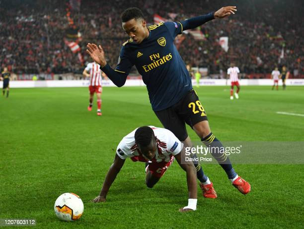 Joe Willock of Arsenal challenges Ousseynou Ba of Olympiacos during the UEFA Europa League round of 32 first leg match between Olympiacos FC and...