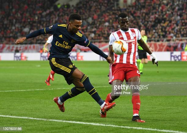 Joe WIllock of Arsenal has his cross blocked by Ousseynou Ba of Olympiacos during the UEFA Europa League round of 32 first leg match between...