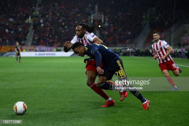 Joe Willock of Arsenal holds off Rúben Semedo of Olympiacos during the UEFA Europa League round of 16 first leg match between Olympiacos FC and...