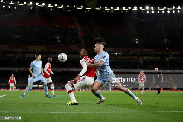 Joe Willock of Arsenal in action with Kalvin Phillips of Leeds United during the FA Cup Third Round match between Arsenal and Leeds United at...