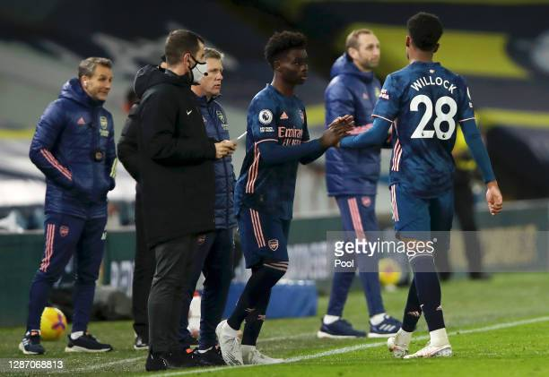 Joe Willock of Arsenal is replaced by Bukayo Saka of Arsenal during the Premier League match between Leeds United and Arsenal at Elland Road on...