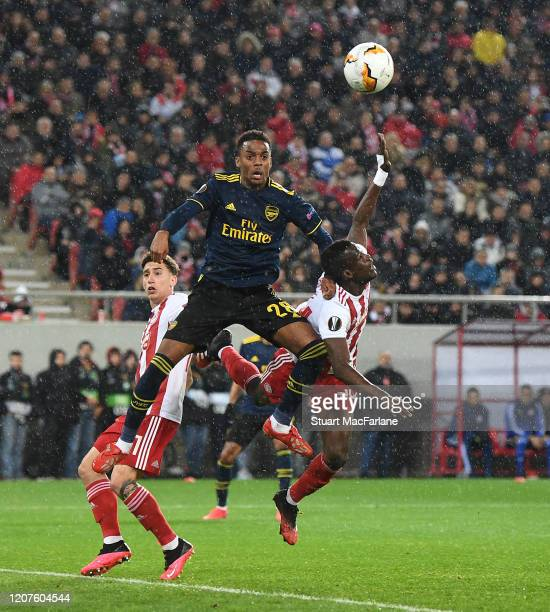 Joe Willock of Arsenal outjumps Ousseynou Ba of Olympiacos during the UEFA Europa League round of 32 first leg match between Olympiacos FC and...