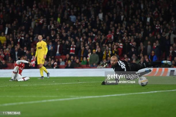 Joe Willock of Arsenal scores his team's third goal past Vanja MilinkovicSavic of Standard Liege during the UEFA Europa League Group F match between...