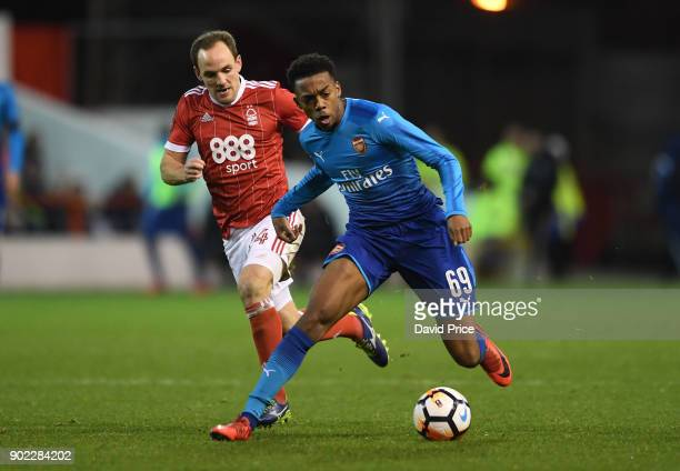 Joe Willock of Arsenal takes on David Vaughan of Forest during the Emirates FA Cup 3rd Round match between Nottingham Forest and Arsenal at City...