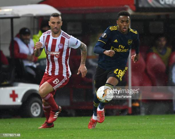 Joe Willock of Arsenal takes on Guilherme of Olympiacos during the UEFA Europa League round of 32 first leg match between Olympiacos FC and Arsenal...
