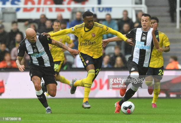 Joe Willock of Arsenal takes on Jonjo Shelvey and Javier Manquillo of Newcastle during the Premier League match between Newcastle United and Arsenal...