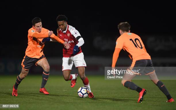 Joe Willock of Arsenal takes on Jordan Holsgrove and Joel Rollinson of Reading during the Premier League International Cup match between Arsenal and...