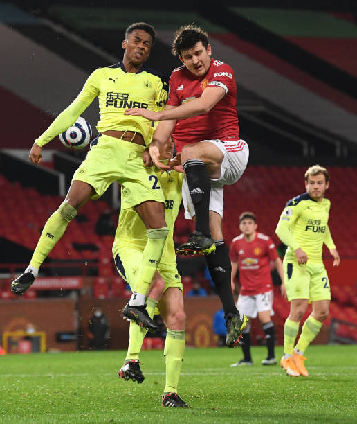 Joe Willock of Newcastle challenges Harry Maguire of Manchester United to the ball during the Premier League match between Manchester United and...
