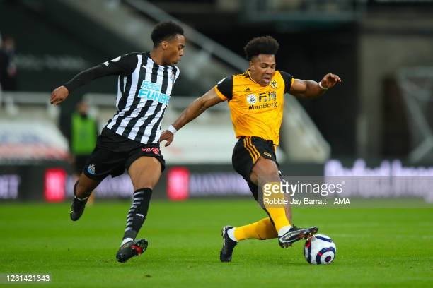 Joe Willock of Newcastle United and Adama Traore of Wolverhampton Wanderers during the Premier League match between Newcastle United and...