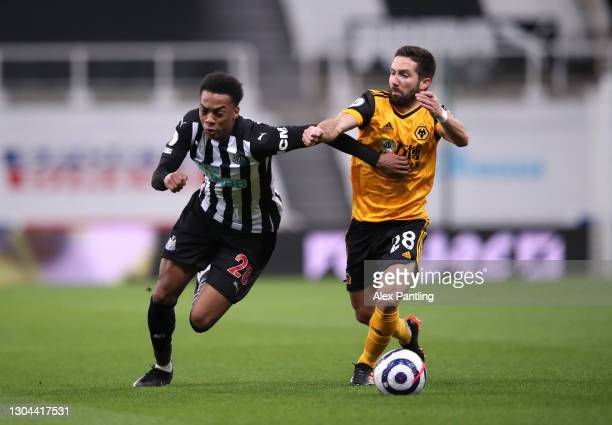Joe Willock of Newcastle United and Joao Moutinho of Wolverhampton Wanderers battle for possession during the Premier League match between Newcastle...