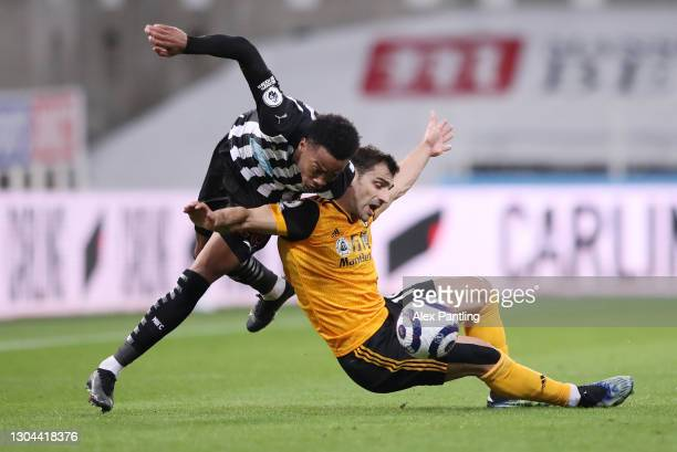 Joe Willock of Newcastle United and Jonny of Wolverhampton Wanderers battle for possession during the Premier League match between Newcastle United...