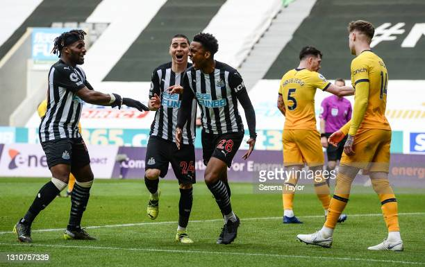 Joe Willock of Newcastle United celebrates after scoring the equalising goal with teammates Allan Saint-Maximin and Miguel Almirón during the Premier...
