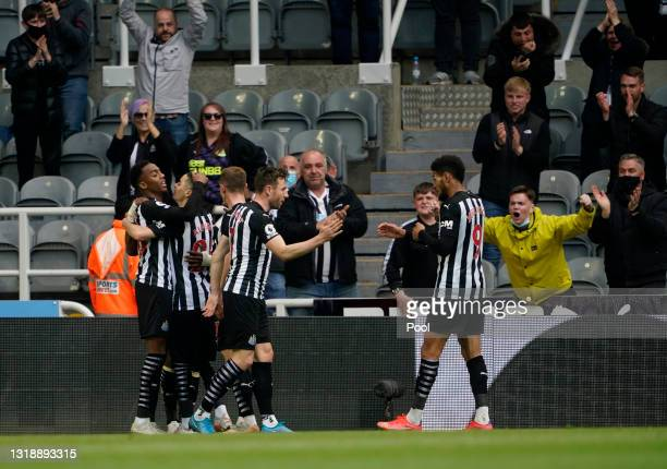 Joe Willock of Newcastle United celebrates with team mates Miguel Almiron, Paul Dummett and Joelinton after scoring his team's first goal during the...