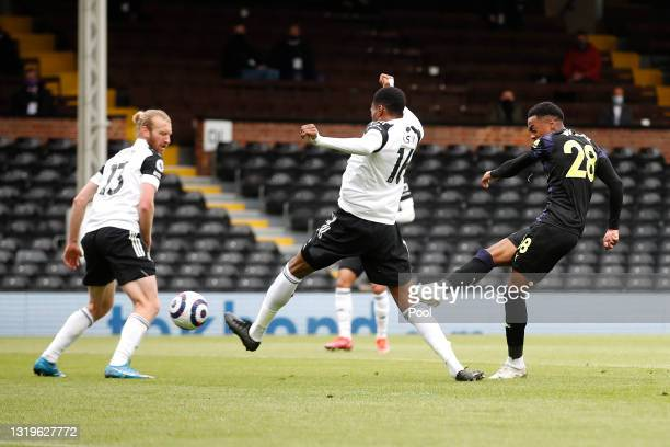 Joe Willock of Newcastle United scores their sides first goal whilst under pressure from Tosin Adarabioyo of Fulham during the Premier League match...