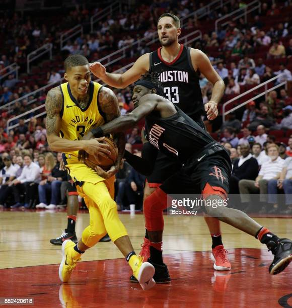 Joe Young of the Indiana Pacers is wrapped up by Briante Weber of the Houston Rockets for a jump ball in the fourth quarter as Ryan Anderson looks on...