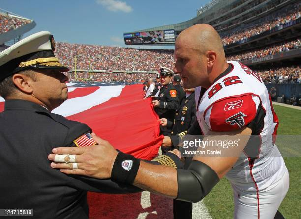 Joe Zelenka of the Atlanta Falcons shakes hands with a fireman during a 9/11 ceremony before the Falcons took on the Chicago Bears at Soldier Field...