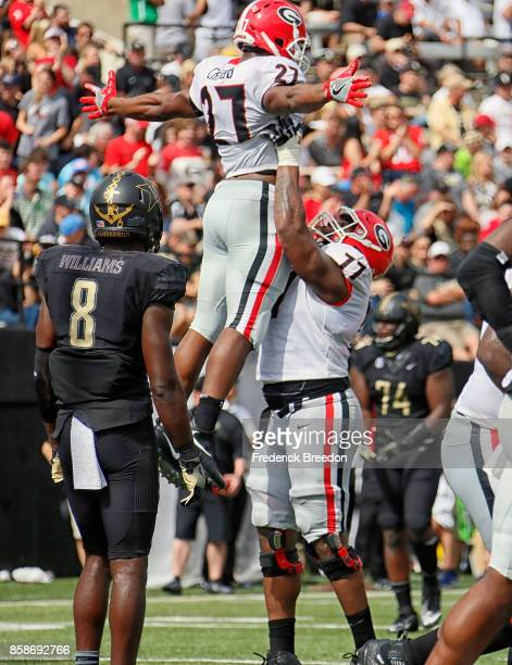 Joejuan Williams of the Vanderbilt Commodores watches as Isaiah Wynn of the Georgia Bulldogs lifts teammate Nick Chubb into the air after a Bulldog...