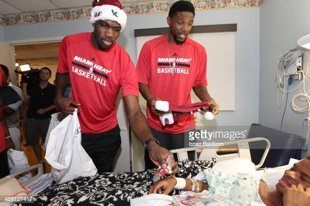 Joel Anthony and Udonis Haslem of the Miami Heat hand out present during a holiday hospital visit on December 19 2013 at the Holtz Childrens Hospital...