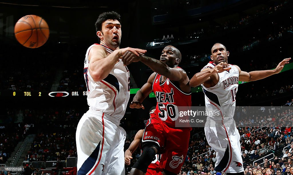 Joel Anthony #50 of the Miami Heat battles for a rebound against Zaza Pachulia #27 and Al Horford #15 of the Atlanta Hawks at Philips Arena on February 20, 2013 in Atlanta, Georgia.