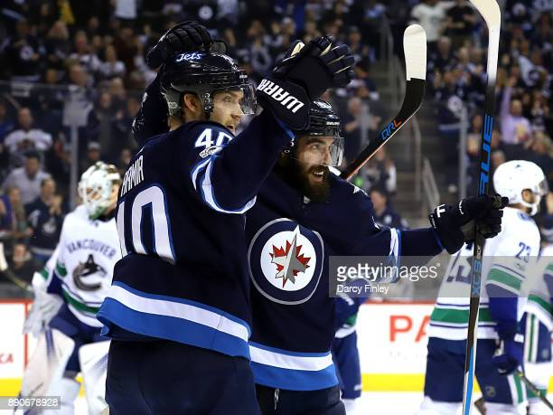 Joel Armia and Mathieu Perreault of the Winnipeg Jets celebrate a second period goal against the Vancouver Canucks at the Bell MTS Place on December...