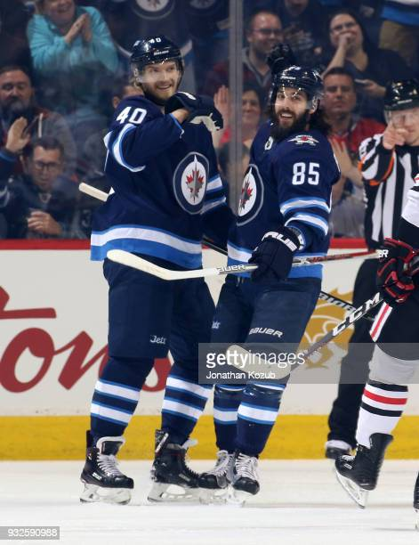 Joel Armia and Mathieu Perreault of the Winnipeg Jets celebrate a first period goal against the Chicago Blackhawks at the Bell MTS Place on March 15...