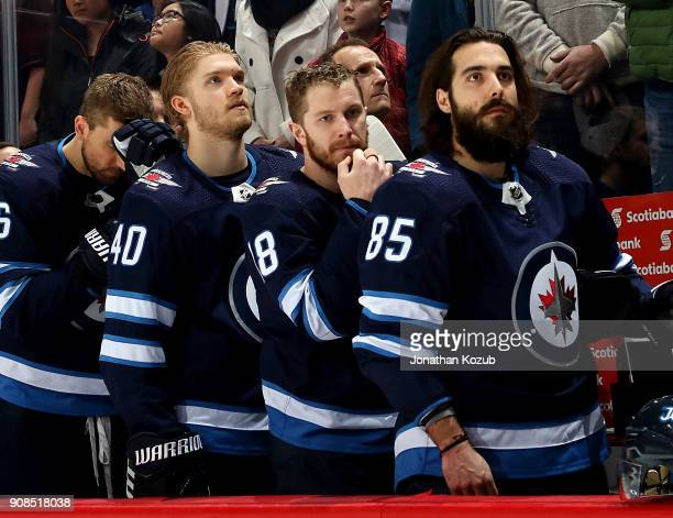 Joel Armia Bryan Little and Mathieu Perreault of the Winnipeg Jets look on from the bench during the singing of 'O Canada' prior to puck drop against...