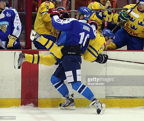Joel Armia of Team Finland hits Rasmus Bengtsson of Team Sweden into the boards at the USA hockey junior evaluation camp at the Lake Placid Olympic...