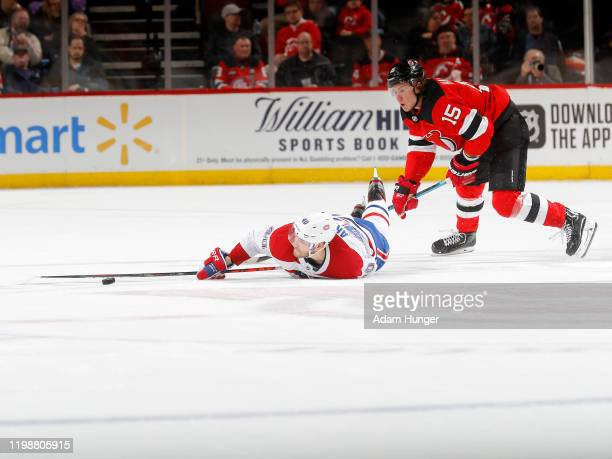 Joel Armia of the Montreal Canadiens reaches for the puck as he is taken to the ice by John Hayden of the New Jersey Devils during the second period...