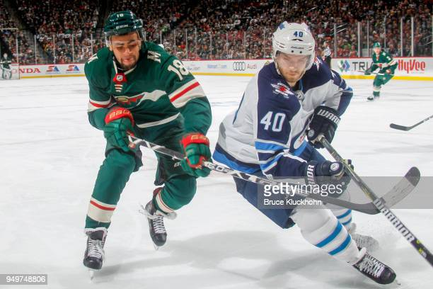 Joel Armia of the Winnipeg Jets and Jordan Greenway of the Minnesota Wild battle for the puck in Game Three of the Western Conference First Round...