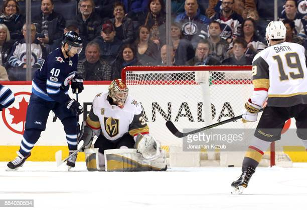 Joel Armia of the Winnipeg Jets and Reilly Smith of the Vegas Golden Knights watch as the puck gets past goaltender Maxime Lagace for a first period...