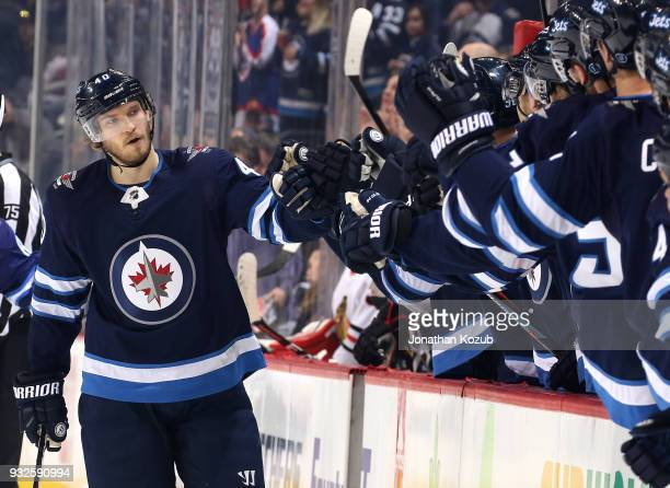 Joel Armia of the Winnipeg Jets celebrates his first period goal against the Chicago Blackhawks with teammates at the bench at the Bell MTS Place on...