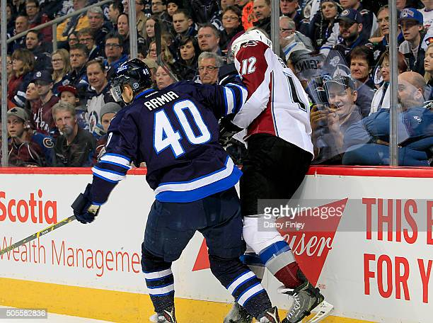 Joel Armia of the Winnipeg Jets checks Jarome Iginla of the Colorado Avalanche into the boards during first period action at the MTS Centre on...