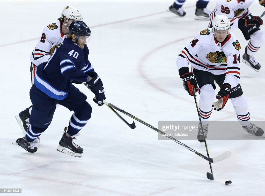 Joel Armia #40 of the Winnipeg Jets checks Victor Ejdsell #14 of the Chicago Blackhawks during NHL action on April 7, 2018 at Bell MTS Place in Winnipeg, Manitoba.