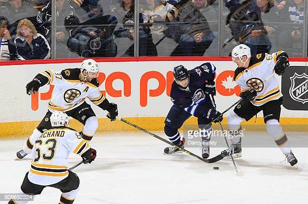 Joel Armia of the Winnipeg Jets plays the puck among Brad Marchand Patrice Bergeron and Zach Trotman of the Boston Bruins during second period action...
