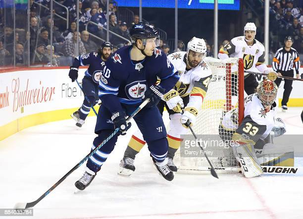 Joel Armia of the Winnipeg Jets plays the puck around the net as PierreEdouard Bellemare and goaltender Maxime Lagace of the Vegas Golden Knights...