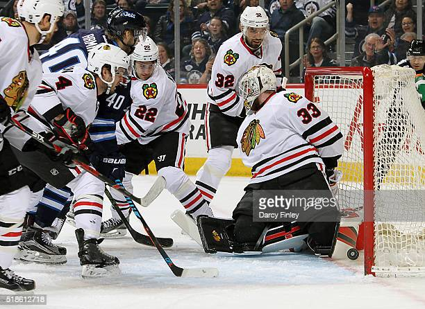Joel Armia of the Winnipeg Jets positions himself among Chicago Blackhawks players as teammate Nic Petan pokes the puck into the net behind...